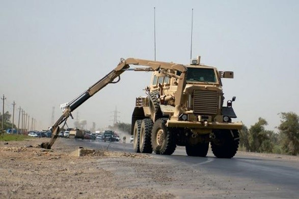 Force Protection Buffalo IED and Mine Clearance MRAP removing an explosive devise by use of its articulated, hydraulically-operated claw.