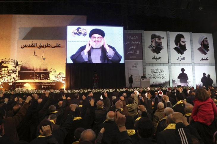 Lebanons Hezbollah leader Sayyed Hassan Nasrallah greets his supporters through giant screen
