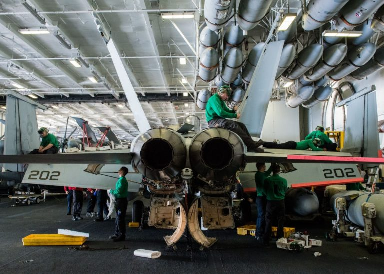 Maintenance crews performing repairs on an F/A-18 aboard a carrier. The U.S. Navy and Marine Corps must address the maintenance crisis plaguing the services, yet the problem cannot be remedied at this level. Only a reduction in the tempo of deployments, flight operations or the provision of added funding will alleviate the issue which will be determined by the White House and Congress.